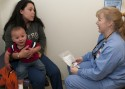 Lisa Casaus, with her son, Gabriel Sanchez, learns tips on good dental hygiene from Children's Hospital dental hygienist Valerie Haustein. Photo Credit: Robert D. Tonsing/Colorado Public News
