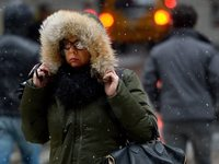 Trying to stay warm, a woman in New York City hung on to her hood Friday.