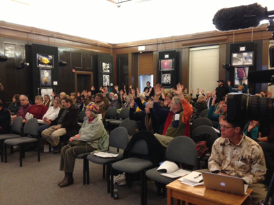 Attendees at the council meeting waved their hands as a form of applause during the public comment session. (Photo: Liz Ruskin)