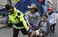 Medical responders run an injured man past the finish line the 2013 Boston Marathon following an explosion in Boston on Monday.