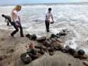 Adam Alvarado, Ashley Priest and Jimmy Garcia create a stone cross near the home of former NFL star Junior Seau&#039;s beach home in Oceanside, Calif. Seau killed himself with with a gun in May 2012.