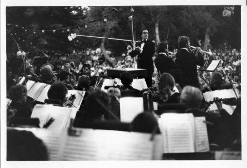[Colorado Springs Symphony] by Myron Wood, June 1976. Copyright PPLD. Image number 002-1696. The Colorado Springs Symphony Orchestra, led by conductor Charles Ansbacher, giving a concert in a park under the trees in front of a large crowd.